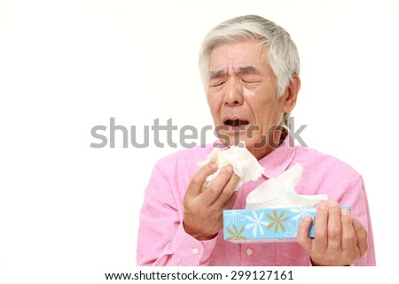 senior Japanese man with an allergy sneezing into tissue - stock photo