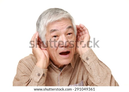 senior Japanese man with hand behind ear listening closely - stock photo