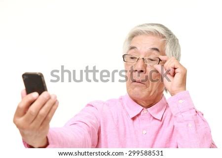 senior Japanese man with presbyopia - stock photo