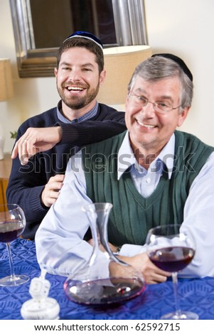 Senior Jewish man and adult son celebrating Hanukkah - stock photo