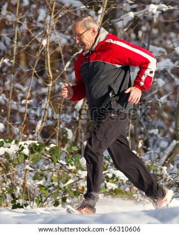 senior jogging in the snow - stock photo