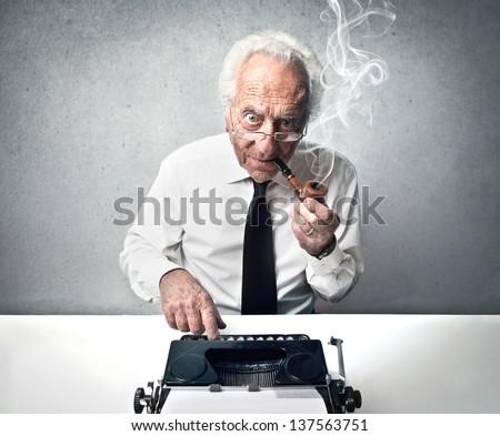 senior journalist writes with vintage typewriter - stock photo