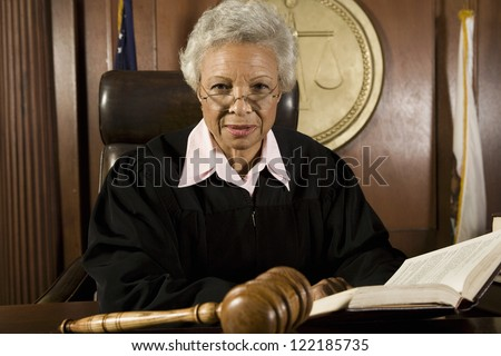 Senior judge sitting with book in courtroom - stock photo