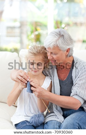 Senior knitting with her granddaughter at home - stock photo
