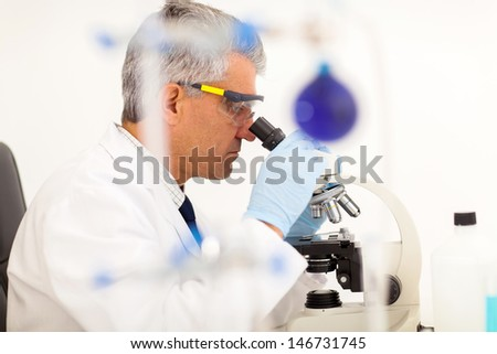 senior lab technician using microscope in laboratory  - stock photo