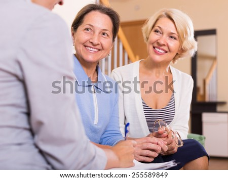 Senior ladies signing documents with agent and smiling - stock photo