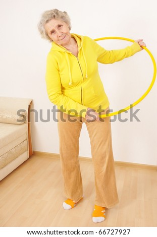 senior lady doing gymnastic with hula-hoop - stock photo
