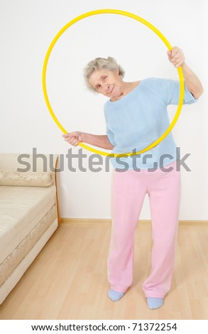 senior lady doing gymnastic with hula-hoop - stock photo