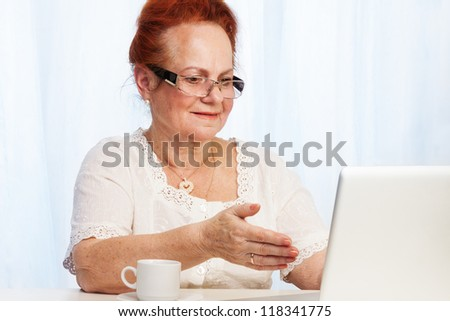 Senior lady found something interesting browsing the internet - stock photo