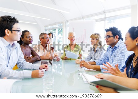 Senior Lady Giving an idea to her Colleagues - stock photo