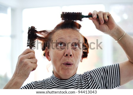Senior lady hairdressing with many combs - stock photo