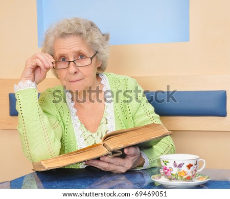 senior lady holding a book for reading - stock photo