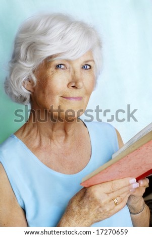 Senior lady holding a book for reading, cyan colors - stock photo