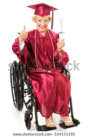 Senior lady in a wheelchair earns her college degree and gives a thumbs up.  Full body isolated on white.   - stock photo