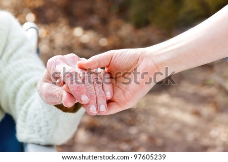 Senior Lady in a Wheelchair Holding Hands with her Young Caretaker - stock photo