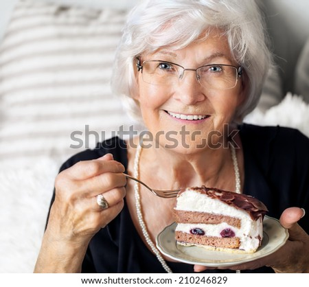 Senior lady looking happy at camera, she likes to eat a piece of cream cake  - stock photo