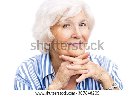 Senior lady looking relaxed at camera with interlaced fingers - stock photo