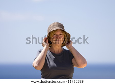 Senior Lady on Holiday - Holding Sun Hat on in the Wind