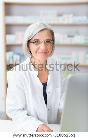 Senior lady pharmacist wearing glasses at work in the pharmacy standing behind the counter and computer smiling at the camera - stock photo