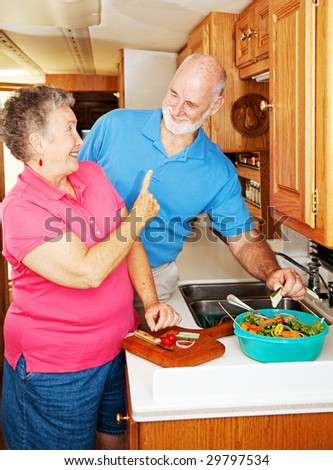 Senior lady playfully scolding her husband for snatching a cucumber from the salad she is making. - stock photo