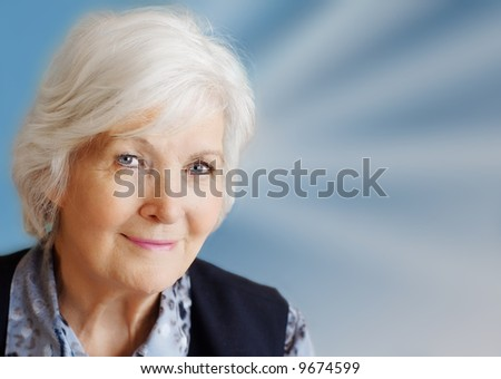 Senior lady portrait on blue with beams - stock photo