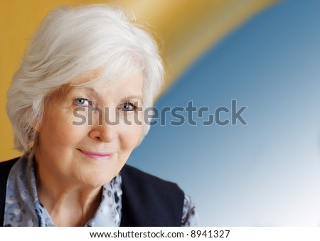 Senior lady portrait on yellow -blue background - stock photo