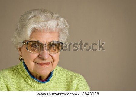 Senior lady portrait, smiling, with glasses, with copy space. - stock photo