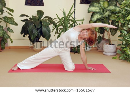 Senior lady practicing yoga in yoga school - stock photo