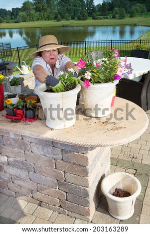 Senior lady preparing ornamental plant pots to decorate her outdoor patio bedding down the new plants with rich compost and soil in a summer kitchen in a rural garden with a lake - stock photo