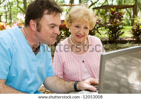 Senior lady receiving help on the computer from a nursing home orderly. - stock photo