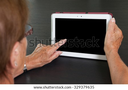 Senior lady relaxing and reading the screen of her tablet, black screen visible - stock photo