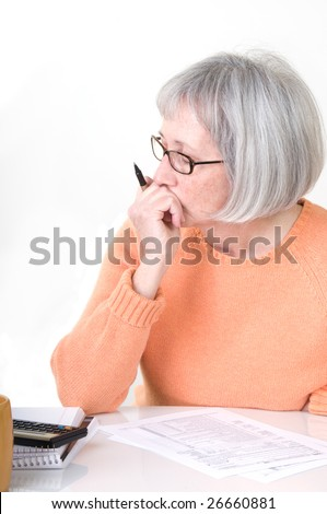 Senior lady sitting at desk with her tax form and calculator and worrying about paying her taxes