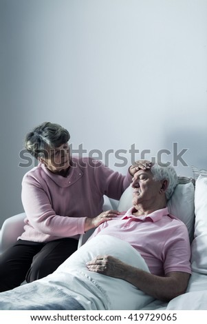 Senior lady taking care of her sick husband lying in hospital bed - stock photo