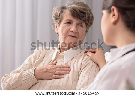 Senior lady talking with her young lovely carer - stock photo