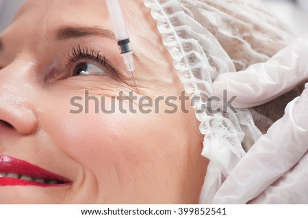 Senior lady wants to get rid of her wrinkles - stock photo