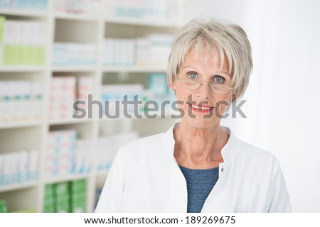 Senior lady wearing glasses working as an assistant or pharmacist in a pharmacy standing looking at the camera against a backdrop of fully stocked shelves - stock photo