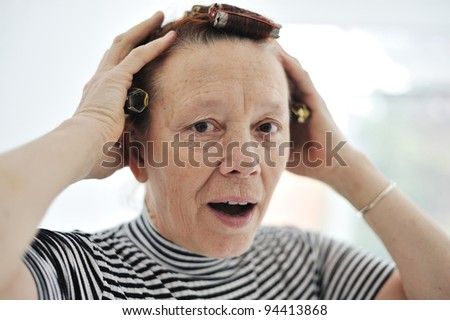 Senior lady with curlers on hair - stock photo