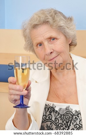 senior lady with goblet of champagne at home
