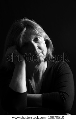Senior Lady with her head on her arm against a black background - stock photo
