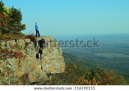 Senior Lady with silver gray hair looking across valley from large rock outcrop along Ozark Mountains Hiking Trail.  Mount Magazine State Park in Arkansas. - stock photo