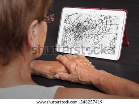 Senior lady with tablet, cracked screen, concept of insurance - stock photo