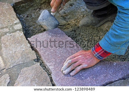 senior landscape gardener fitting a flagstone tile with a rubber mallet - stock photo