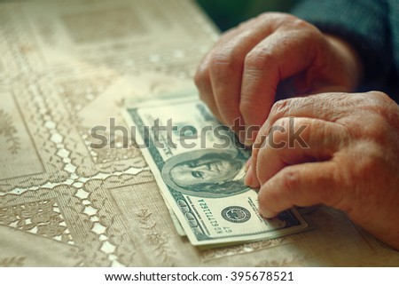 Senior latino female with little amount of money, toned image, colorized, selective focus, very shallow dof - stock photo
