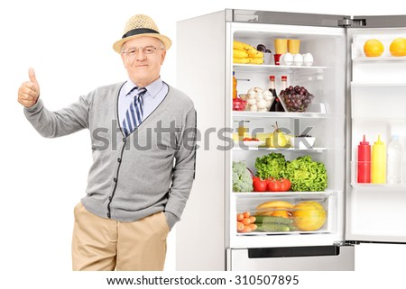 Senior leaning on a fridge and giving thumb up isolated on white - stock photo
