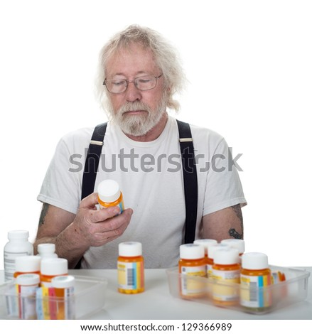 Senior looking at a bottle of pills with more bottles of pills on a table isolated on white