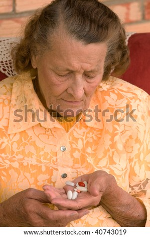 senior looking down at a handful of pills - stock photo