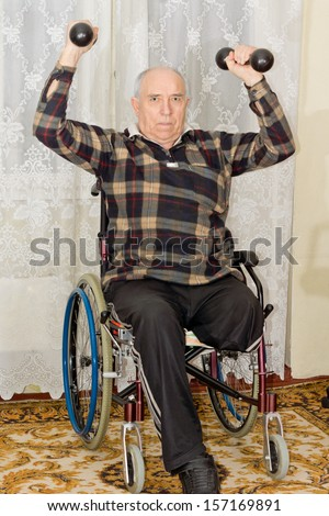 Senior male amputee working out lifting weights in his wheelchair holding a pair of dumbbells above his head to tone his muscles - stock photo