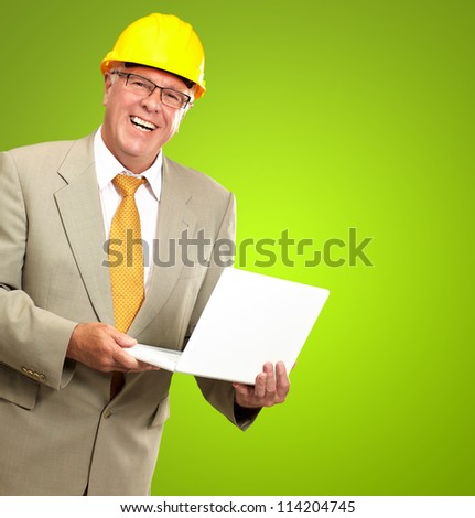 Senior Male Architect Holding Laptop On Green Background - stock photo