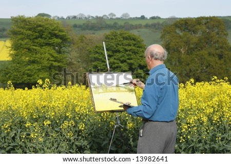 Senior male artist painting in a field full of bright yellow rapeseed or canola. - stock photo