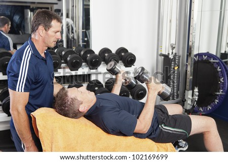 Senior male being spotted by personal trainer - stock photo
